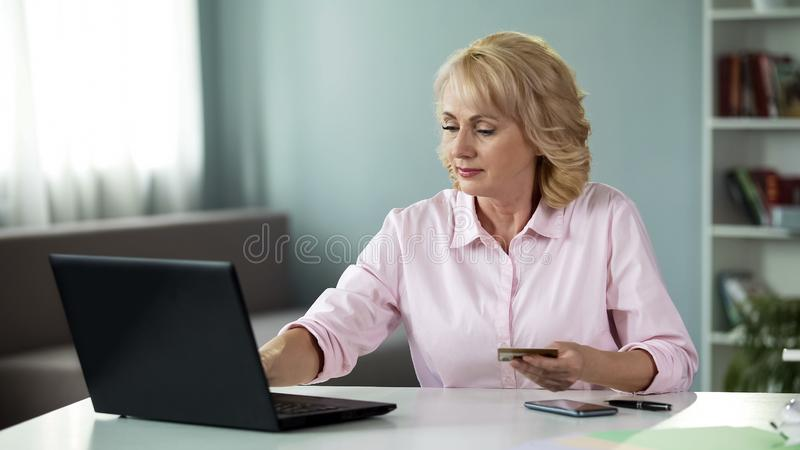 Kvinna över 50 skrivande in data av hennes kort som direktanslutet betalar för nytto- service arkivfoton