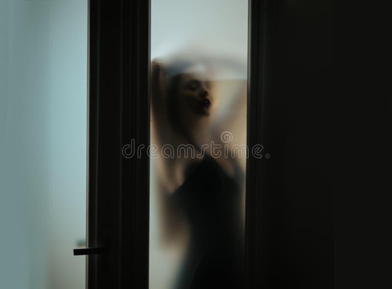 Kvinna bak oskarpt exponeringsglas Defocused oskarp bild fotografering för bildbyråer