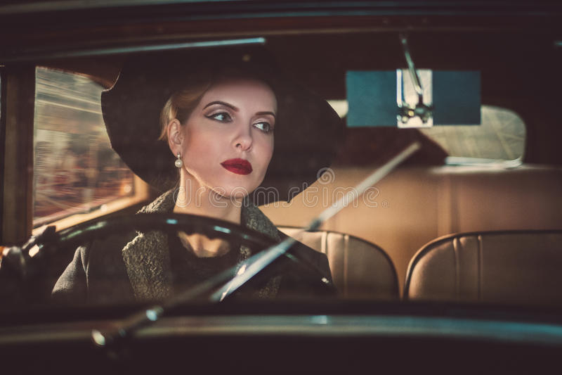 Kvinna bak styrninghjulet av en retro bil arkivbild