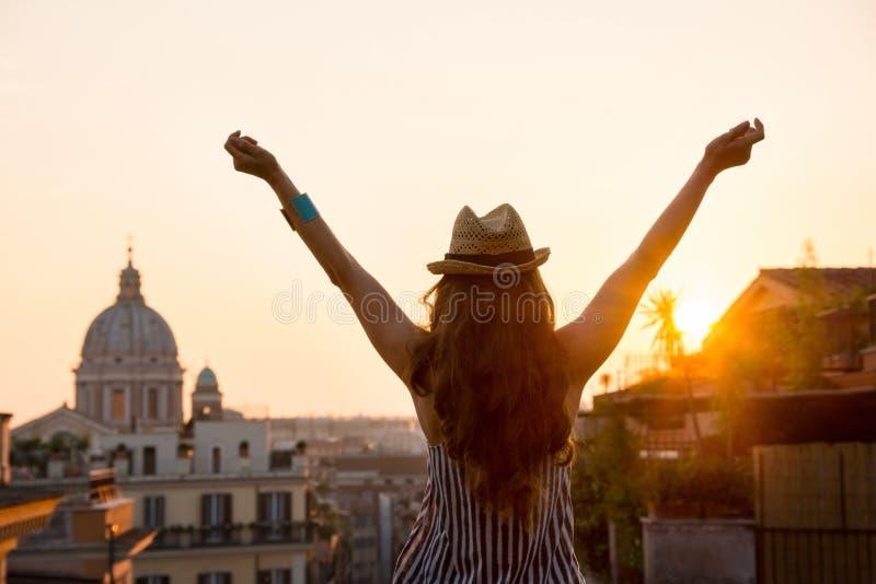 Kvinna bakifrån med utsträckta armar i Rome på solnedgången royaltyfri fotografi