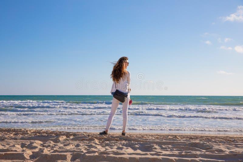 Kvinna bakifrån på kusten av stranden av havet som ser till royaltyfria foton