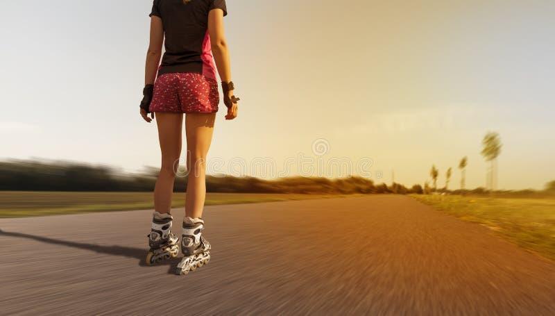 Kvinna bakifrån som åker skridskor i gatan arkivfoto