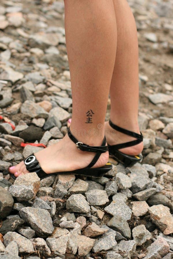 Kvinna ben med hieroglyphtatueringen arkivfoto
