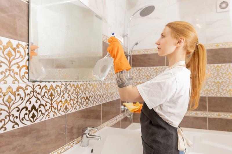 Kvinna desinficerar badrummets yta från virus, damm och smuts från bakterier Rengöring av hus arkivbild