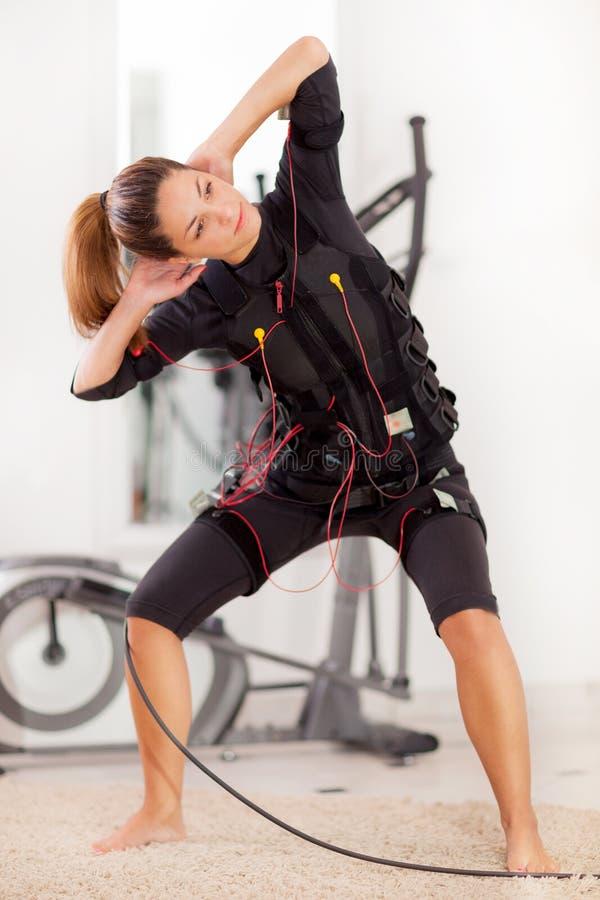 Kvinna electro muskulös stimulansövning för ems arkivbild