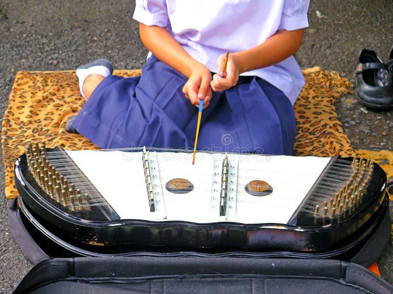 Kvinna- eller flickasammanträde och spelacymbal royaltyfri foto