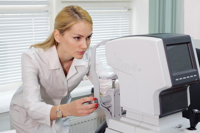 Kvinna för ögondoktor med den ophthalmologic apparaten i kabinettet arkivfoto