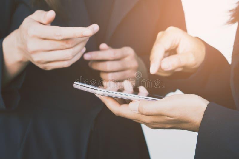 Kvinna för affär som två ser mobiltelefonen som talar om deras projekt royaltyfria bilder