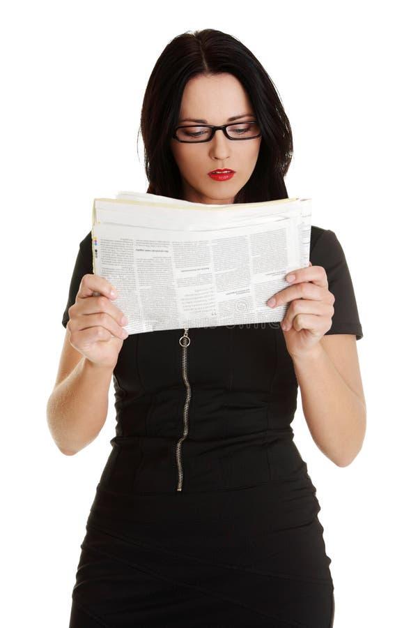 kvinna för avläsning för affärstidning arkivfoto