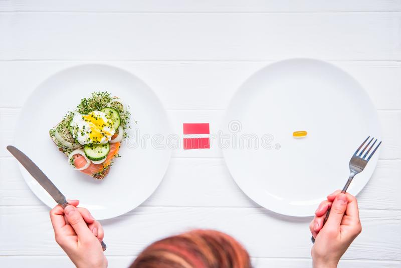 Kvinna för bästa sikt som väljer mellan sund mat eller läkarundersökningpreventivpilleren på vitplattorna och trätabellen Val ell arkivfoton