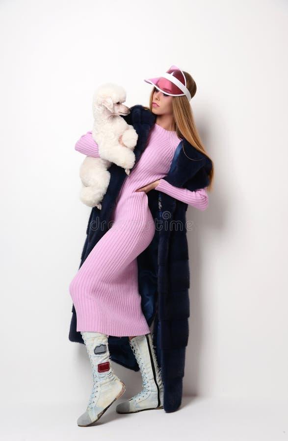 Kvinna för barnmodeglamour i rosa lång hållande vit pudelhund för blus och för hatt royaltyfria foton