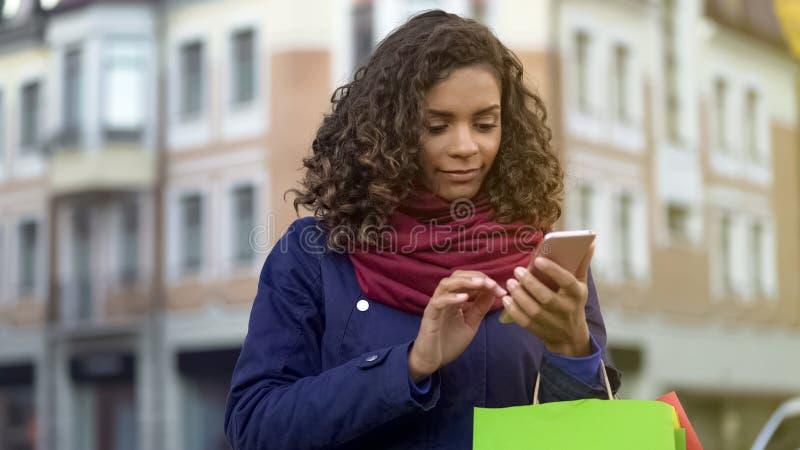 Kvinna för blandat lopp som kontrollerar online-lagerapps på den moderna smartphonen som shoppar royaltyfria foton