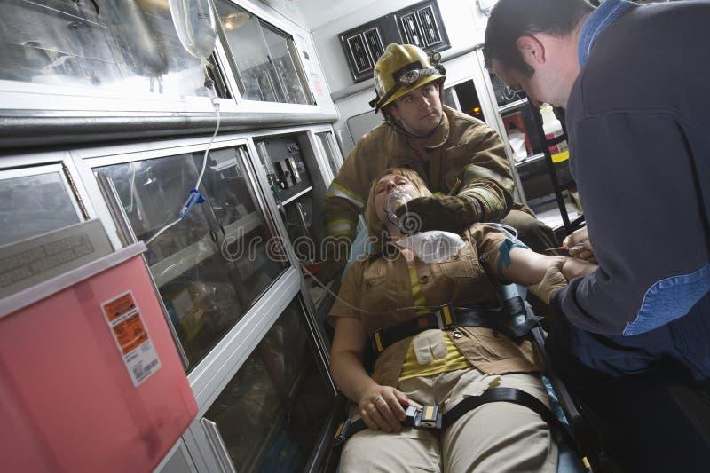 Kvinna för brandmanAnd EMT doktor Helping An Injured arkivfoto