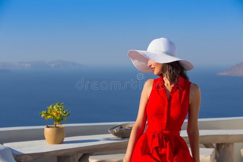 Kvinna för brunett för Santorini lopp turist- i röd klänning som besöker den berömda vita Oia byn royaltyfria bilder