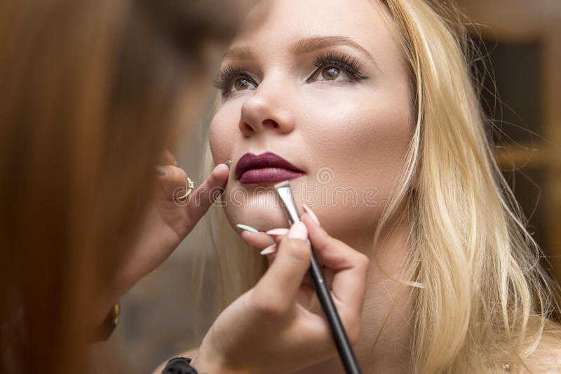 Kvinna för brunettsminkkonstnär som applicerar sminket för en blond brid royaltyfri bild