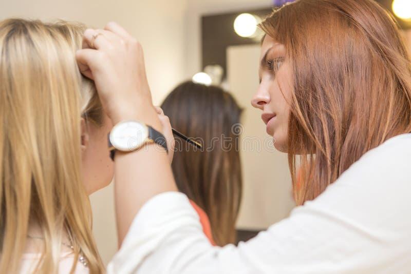 Kvinna för brunettsminkkonstnär som applicerar sminket för en blond brid arkivfoton