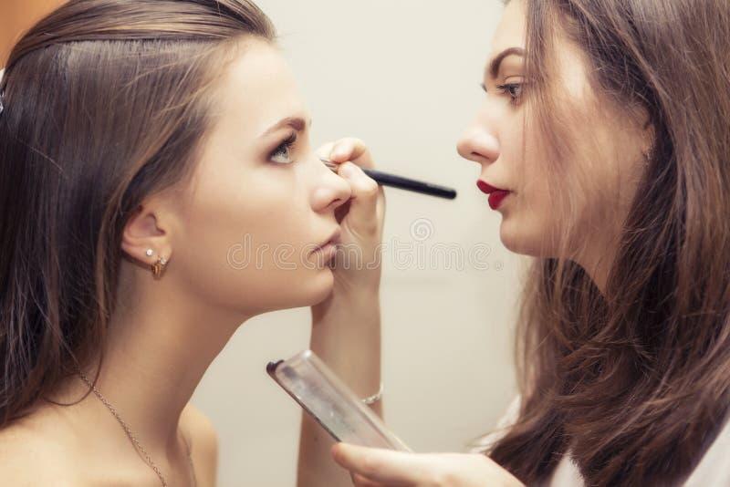 Kvinna för brunettsminkkonstnär som applicerar sminket för en brunettbr royaltyfri foto
