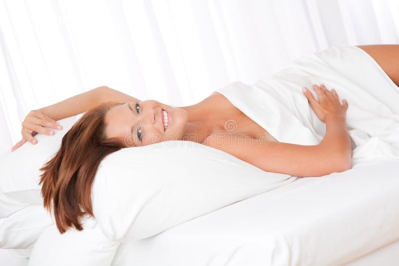 kvinna för brunt hår för underlag liggande le vit arkivfoton