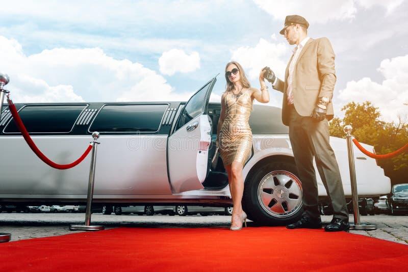 Kvinna för chaufförportionstorgubbe eller stjärna ut ur limoen på röd matta arkivfoto