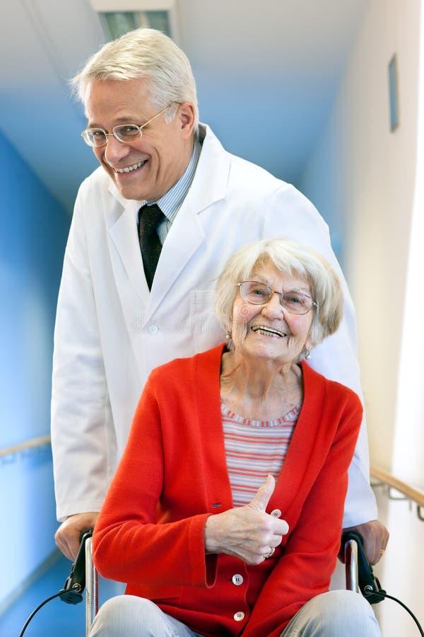 Kvinna för doktor Pushing Happy Elderly i rullstol royaltyfri foto