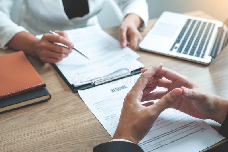 Kvinna för hög chef som läser en meritförteckning under ett sökande och en rekrytering för möte för ung man för anställd för jobb royaltyfri bild