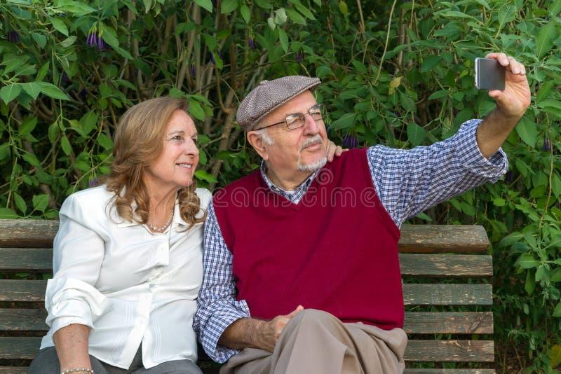 Kvinna för hög man som och pensionärgör ett självporträtt royaltyfri bild