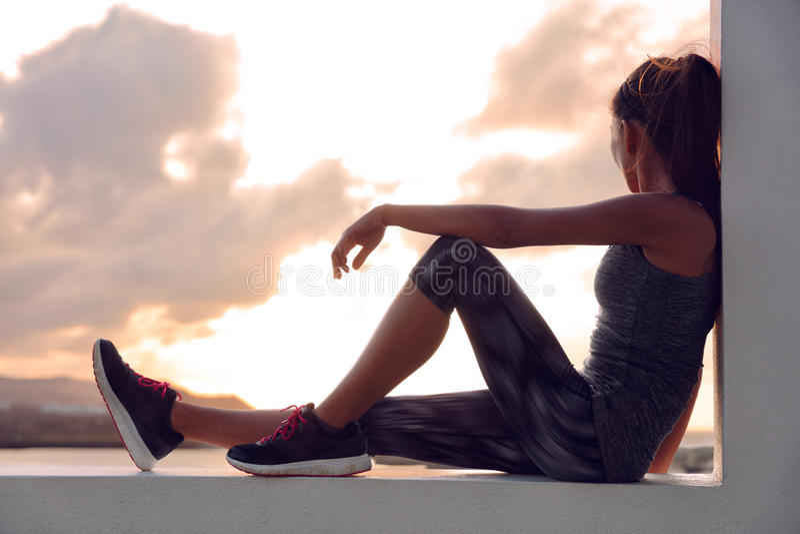 Kvinna för konditionidrottsman nenlöpare som kopplar av i solnedgång royaltyfri bild