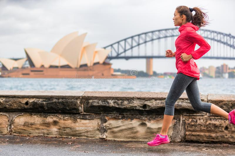 Kvinna för livsstil för löparepassform som aktiv joggar på Sydney Harbour förbi gränsmärket för turist- dragning för operahus den royaltyfri foto