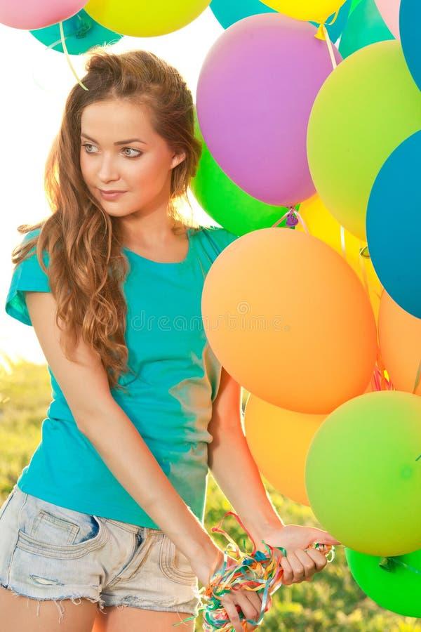 Kvinna för lycklig födelsedag mot himlen med regnbåge-färgade luftlodisar royaltyfri bild