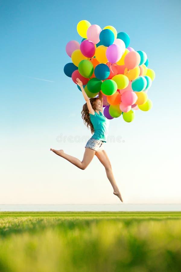 Kvinna för lycklig födelsedag mot himlen med regnbåge-färgade luftlodisar royaltyfria foton