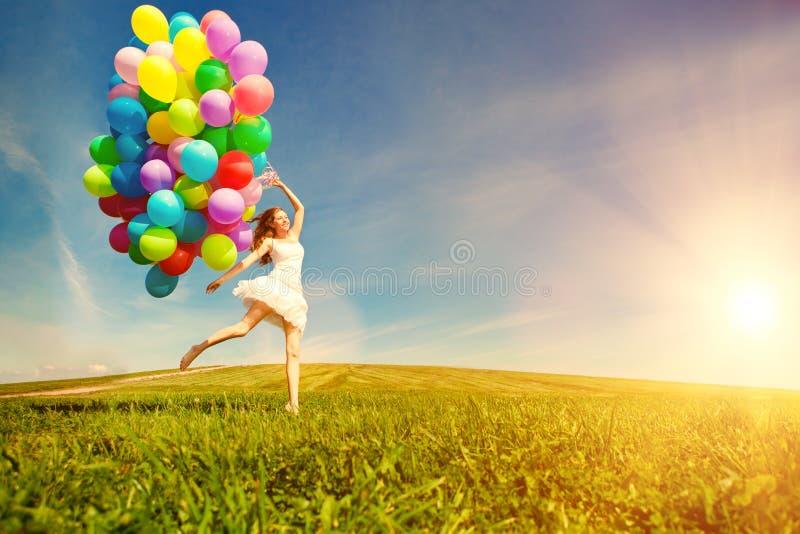 Kvinna för lycklig födelsedag mot himlen med regnbåge-färgade luftlodisar arkivfoton