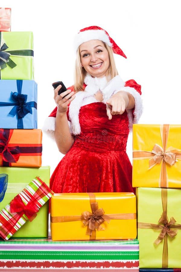 Kvinna för lycklig jul med att peka för telefon royaltyfri fotografi
