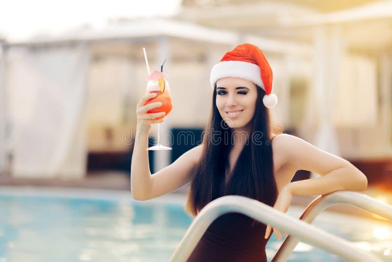 Kvinna för lycklig jul med coctailen på pölen royaltyfria bilder