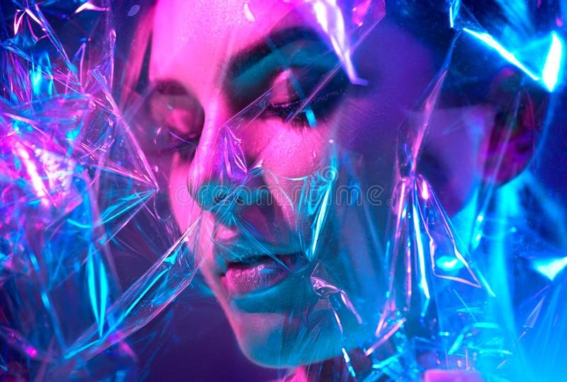 Kvinna för modemodell i färgrika ljusa neonljus som poserar i studio till och med den genomskinliga filmen Stående av den härliga royaltyfria foton