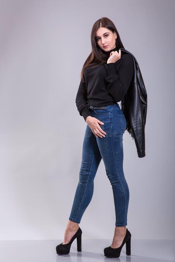 Kvinna för modemodell som poserar i jeans och svartöverkanten som rymmer det svarta läderomslaget på grå bakgrund - studioskott royaltyfria foton