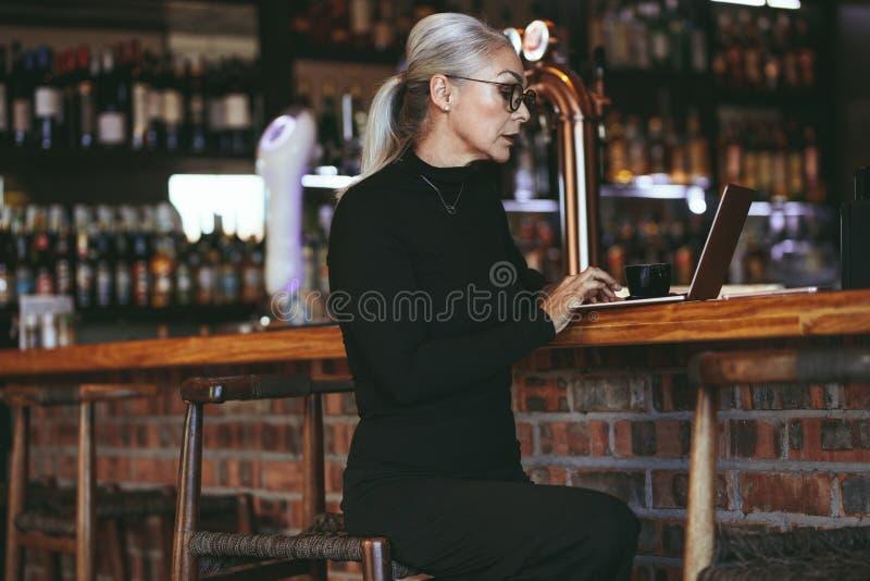 Kvinna för mogen affär på coffee shop med bärbara datorn fotografering för bildbyråer