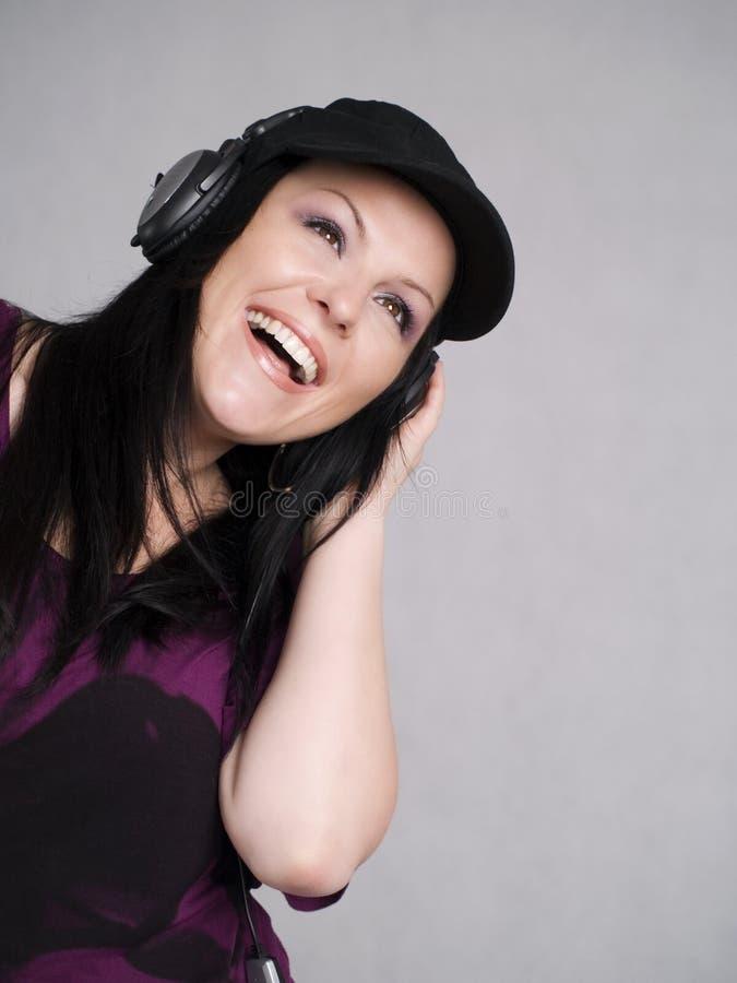 kvinna för musik för hörlurar lyssnande le royaltyfria foton
