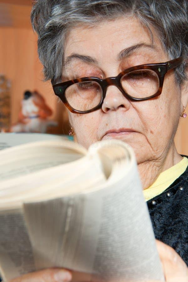 Kvinna För Pensionär För Bokståendeavläsning Royaltyfri Fotografi