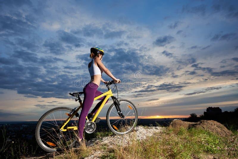 Kvinna för sidosikt med det perfekta diagramet på cykeln som tycker om superb blå himmel med moln och solen på solnedgången royaltyfria bilder