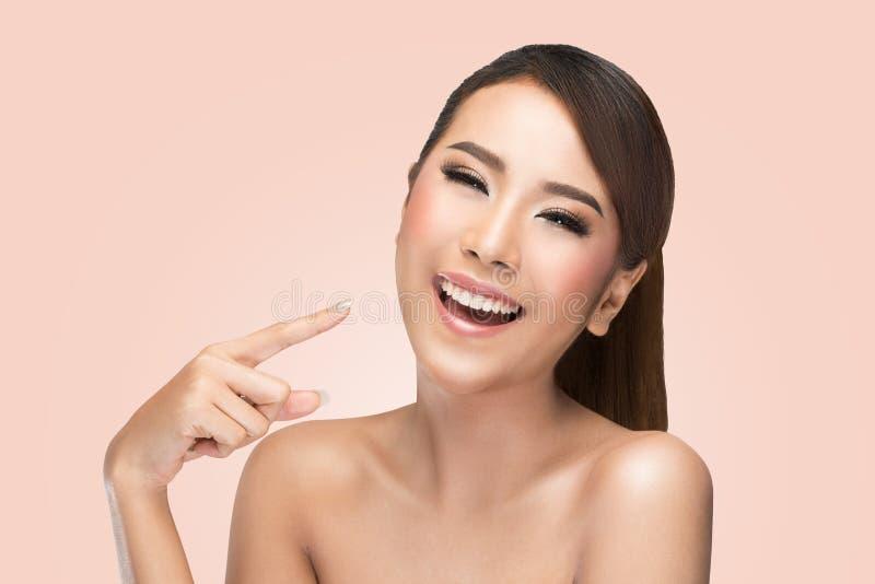 Kvinna för skönhet för hudomsorg som asiatisk pekar hennes framsida och skratta royaltyfri fotografi