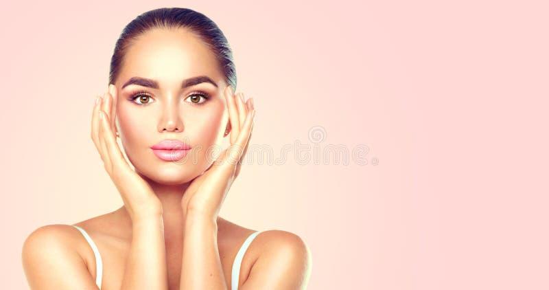 Kvinna för skönhetbrunettbrunnsort som trycker på hennes framsida Skincare royaltyfria bilder