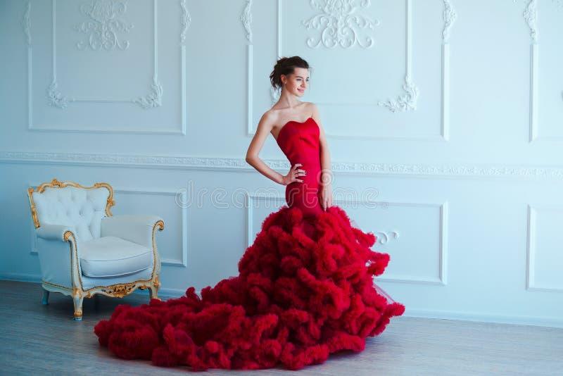 Kvinna för skönhetbrunettmodell i röd klänning för afton Makeup och frisyr för härligt mode lyxig förförisk flicka fotografering för bildbyråer