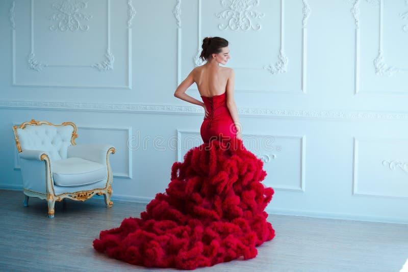 Kvinna för skönhetbrunettmodell i röd klänning för afton Makeup och frisyr för härligt mode lyxig förförisk flicka royaltyfri bild