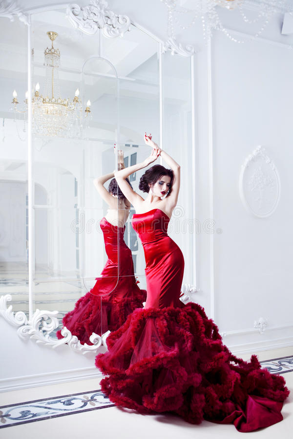 Kvinna för skönhetbrunettmodell i röd klänning för afton arkivfoto