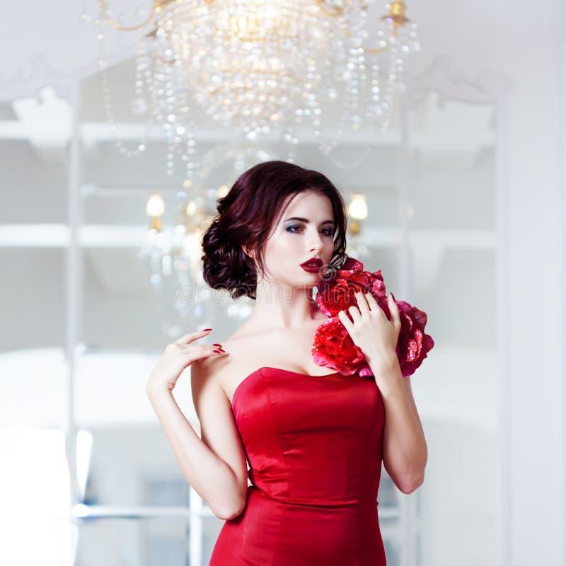 Kvinna för skönhetbrunettmodell i röd klänning för afton arkivbild
