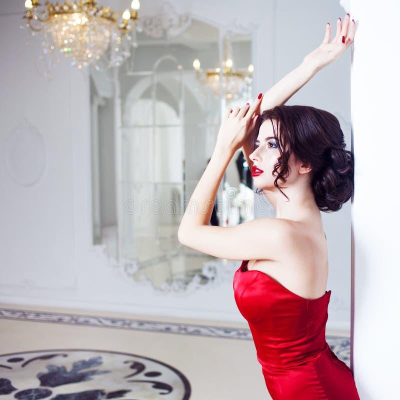 Kvinna för skönhetbrunettmodell i röd klänning för afton fotografering för bildbyråer