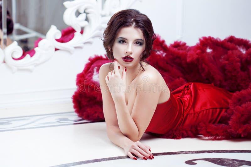 Kvinna för skönhetbrunettmodell i röd klänning för afton arkivfoton