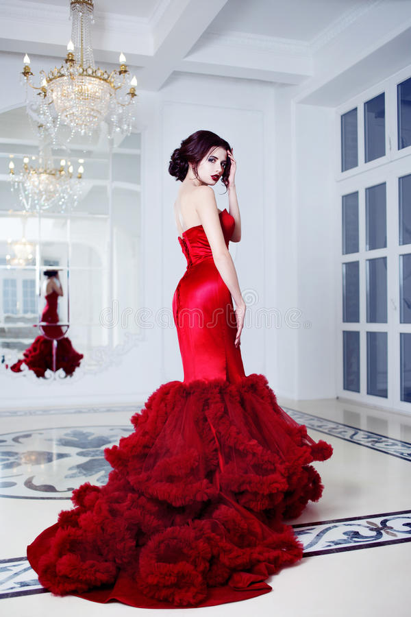 Kvinna för skönhetbrunettmodell i röd klänning för afton royaltyfri fotografi