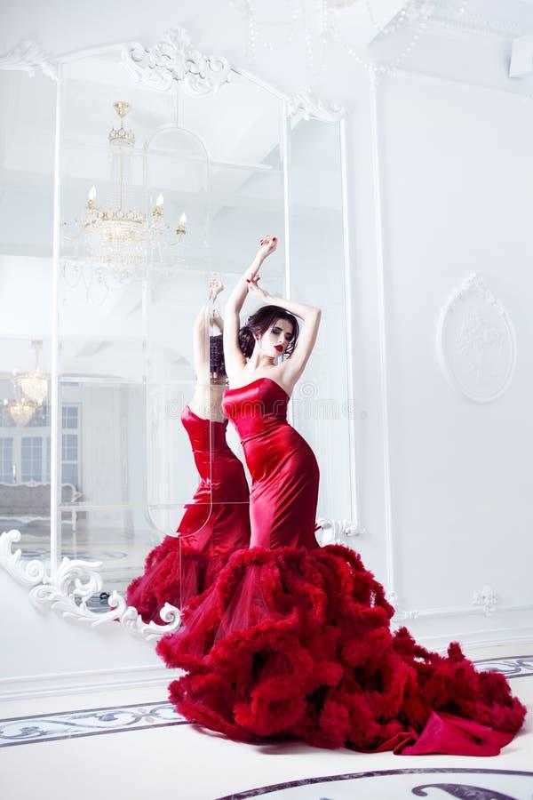 Kvinna för skönhetbrunettmodell i röd klänning för afton royaltyfri bild