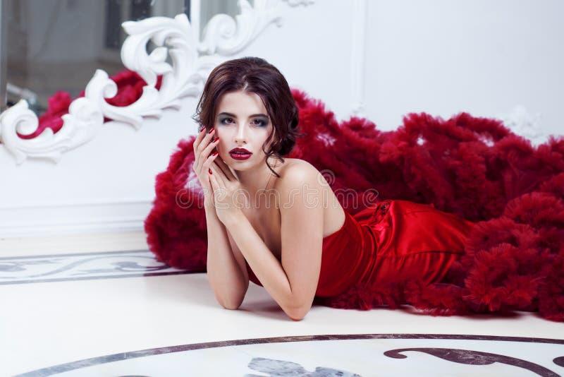 Kvinna för skönhetbrunettmodell i röd klänning för afton royaltyfri foto